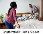 black couple changing bed sheet ... | Shutterstock . vector #1051726535