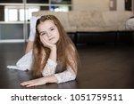 little caucasian girl lies on a ... | Shutterstock . vector #1051759511