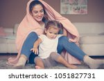 mother and daughter playing in... | Shutterstock . vector #1051827731