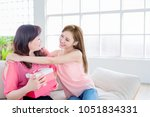 daughter give her mother gift... | Shutterstock . vector #1051834331