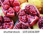 """Small photo of Pomegranate. Red-purple in color, the pomegranate fruit husk has two parts: an outer, hard pericarp, and an inner, spongy mesocarp (white """"albedo""""). It's healthy and fresh."""