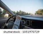 hands on wheel driving car on... | Shutterstock . vector #1051970729