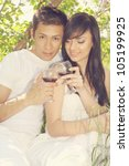 Young man and woman drinking wine under the lilac bush - stock photo