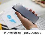 a businessman holds a new... | Shutterstock . vector #1052008019