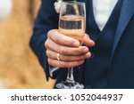 married man holds glass of... | Shutterstock . vector #1052044937