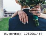 bride holds hands with wedding... | Shutterstock . vector #1052061464