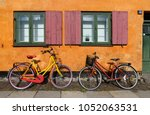 Bicycles In Front Of An Orange...
