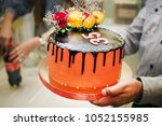 Small photo of a man holds a cake of thirty-five years in his hands