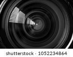 Small photo of Photo Camera or Video lens close-up on black background, objective, concept of photographer camera man job, looking for a photographer, journalist, a videographer to work black and white
