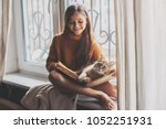 Stock photo child in warm woolen sweater seating on window sill and reading a book winter weekend with cat at 1052251931