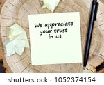 Small photo of We appreciate your trust in us. Text on paper on a wooden table