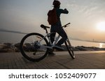 silhouette cyclist use mobile... | Shutterstock . vector #1052409077