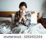 a woman suffering from flu in... | Shutterstock . vector #1052421314