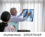 doctor showing a radiography to ... | Shutterstock . vector #1052476169