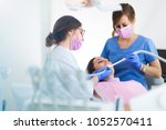 dentists and patient in dentist ... | Shutterstock . vector #1052570411