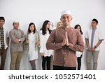 a muslim man standing in front... | Shutterstock . vector #1052571401
