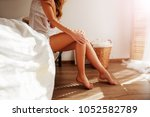Small photo of Relaxed Caucasian Girl is sitting on modern Bed with soft mattress near the window in light. She is enjoying a sunny Spring day and morning. Beautiful female Feet barefoot on the warm floor.