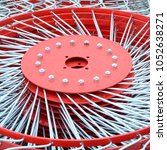Small photo of New red tedder for trailer in agricultural machinery for gathering hay. Close up
