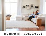 family sitting on sofa at home... | Shutterstock . vector #1052675801