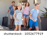 family with luggage leaving... | Shutterstock . vector #1052677919