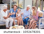 Small photo of Multi Generation Family Enjoy Outdoor Drinks And Snacks At Home