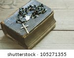 old holy bible and rosary beads on rustic wooden table - stock photo