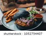 charcoal black bun burger... | Shutterstock . vector #1052754407