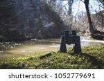 an image of binoculars on grass ...   Shutterstock . vector #1052779691