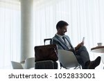 businessman sitting at airport... | Shutterstock . vector #1052833001