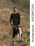 Small photo of Adult muscular man in activewear standing with Husky on leash among rocks and looking away.