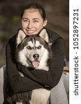 Small photo of Cheerful woman in activewear embracing adorable Husky sitting in sunlight looking away.