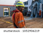 Small photo of Head of AB able seamen - Bosun on deck of offshore vessel or ship , wearing PPE personal protective equipment - helmet, coverall, lifejacket, goggles. He is smiling. Perfect job at sea
