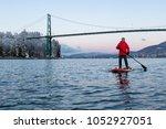 adventurous man on a standup... | Shutterstock . vector #1052927051