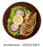 Small photo of grilled chicken fillet with vegetables (lemon, salad, onion) isolated on white background. chicken fillet grilled on a plate top view