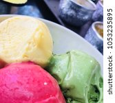 Small photo of Three scoops of colorful ice cream made from fruit juices , pink, yellow, green all together in white bowl