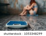 anorexic woman sitting on the... | Shutterstock . vector #1053348299