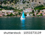 Small photo of Yacht with a blue sail swims along the sea along the coast