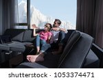 young couple sitting on sofa... | Shutterstock . vector #1053374471