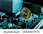 A bitcoin concept with tokens on a computer circuit board showing the currency is virtual - stock photo