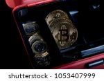 A bitcoin concept of bitcoins in a money box next to regular one poiund coins - stock photo