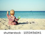 a small child sitting on the... | Shutterstock . vector #1053456041