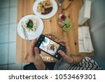 food blogger making photos for... | Shutterstock . vector #1053469301