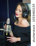 Small photo of Portrait of young woman recording a song in a professional studio. Female vocal