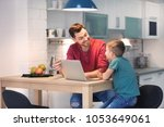 little boy and his dad using... | Shutterstock . vector #1053649061