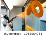 powder coating of metal parts.... | Shutterstock . vector #1053664751