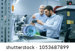 two engineers works with mobile ...   Shutterstock . vector #1053687899