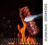 pork ribs over flaming grill... | Shutterstock . vector #1053693341