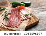 board with raw bacon on table ... | Shutterstock . vector #1053696977