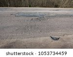 very bad quality road with... | Shutterstock . vector #1053734459