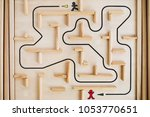 Wooden labyrinth game. The path to the finish is shown as black line. Concept of finding the way out  or overcoming obstacles.